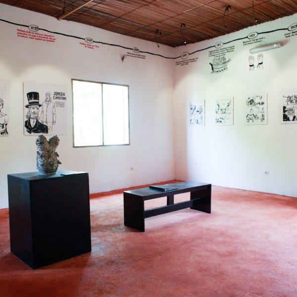 Huone, jossa on musta jalusta jonka päällä on teos. Jalustan vieressä on musta jakkara. Valkoisilla seinillä on tekstiä ja piirrustuksia.