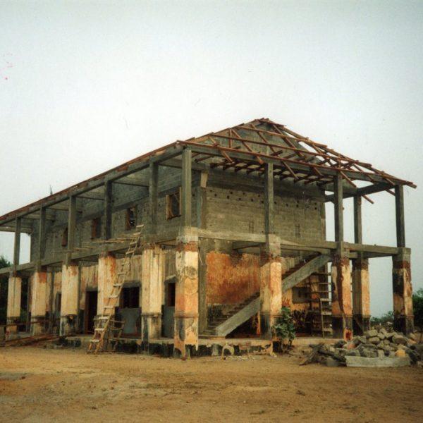 Puolivalmis rakennus keskellä kuvaa. Rakennuksen katto on puinen, muu rakennus on betonia.