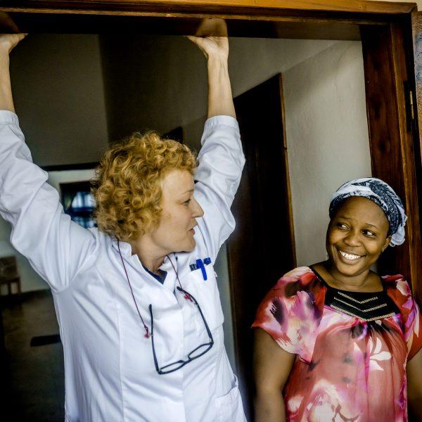 Kaksi naista on oven äärellä. Yhdellä on valkoinen asu ja toisella vaaleanpunainen paita.
