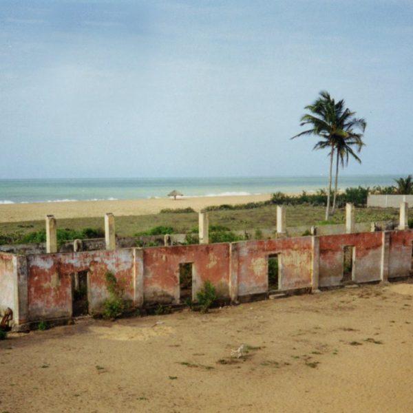 Lissa Gbassan raunio. Takana on ranta ja kaksi palmupuuta.