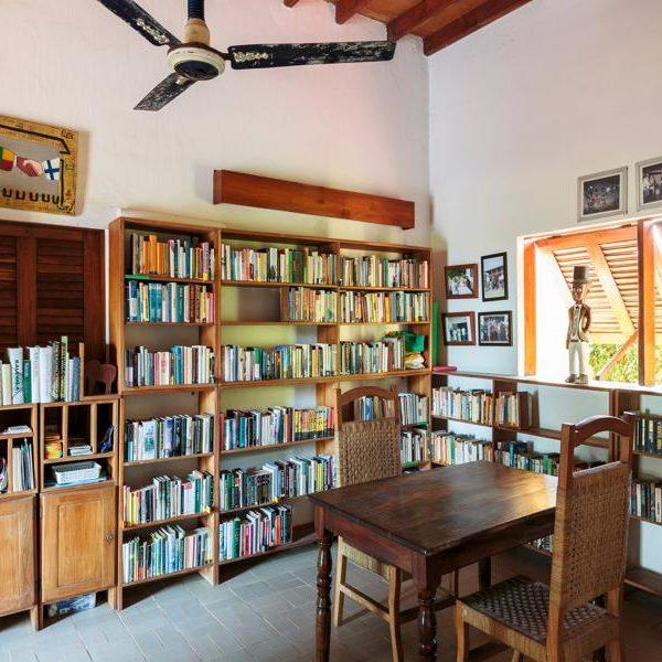 Kirjahylly täynnä kirjoja, pöytä ja kaksi tuolia, tuuletin katossa, ikkunaluukut auki, kuva: Tuomas Uusheimo