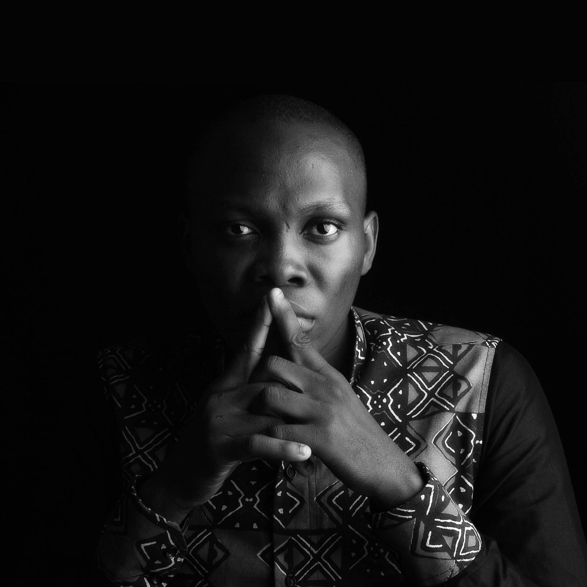 Komy Agboguin; Komy katsoo kameraan kädet ristissä edessä. Kuva on mustavalkoinen.