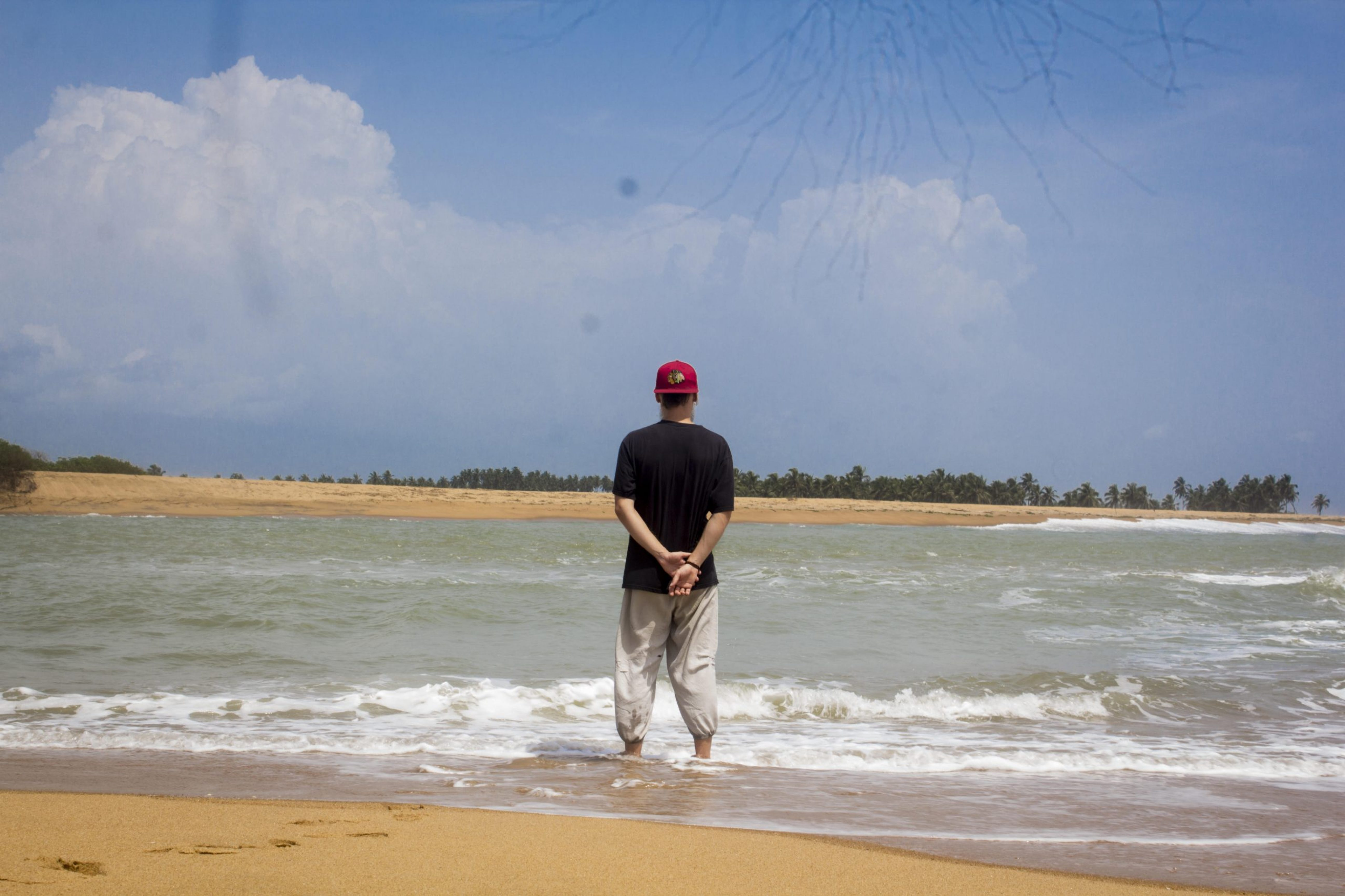Ihminen seisoo veden päällä, kädet takana ja musta paita.
