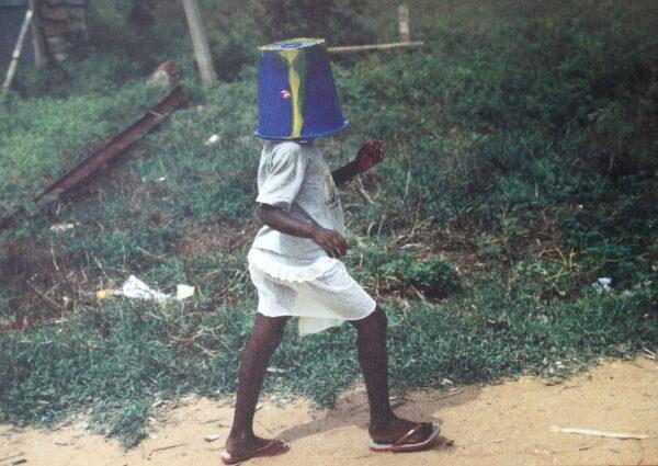 Kuvassa on lapsi kävelemässä polulla. Hänellä on päässâän sininen ämpäri. Taustalla näkyy hieman kuivahtanutta nurmikkoa.
