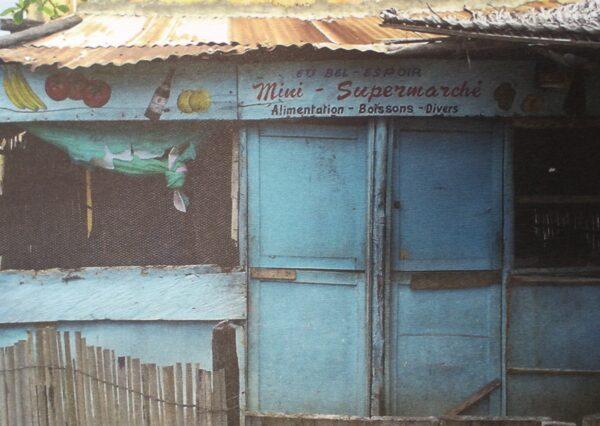 """Kuvassa on sininen pienen kojun ovi, jonka yläpuolella lukee """"Mini-Supermarché, alimentation, boissons, divers"""". Yläpuolelle on myös maalattuna kuvia hedelmistä ja pullosta. Putiikin ikkunat ovat verkkoa."""