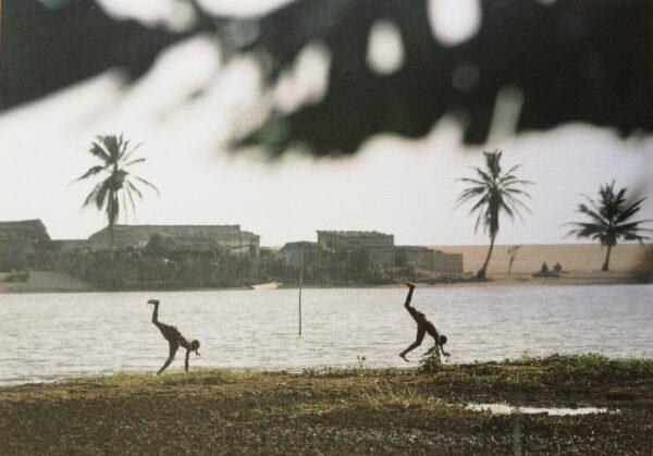 Kuvassa on kaksi ihmistä heittämässä kärrynpyöriä rannalla. Taustalla näkyy joki ja sen takana palmuja ja rakennuksia. Molemmat ihmiset ovat samassa asunnossa. Kuvan yläosassa näkyy myös palmunlehtiä.